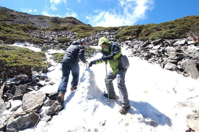 幸が積もった山を登る男性