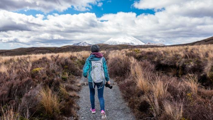草原の中を歩いている女の人の写真