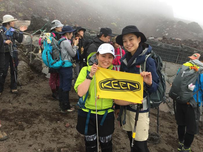 KEENの旗を持って撮影をする登山参加者の女性