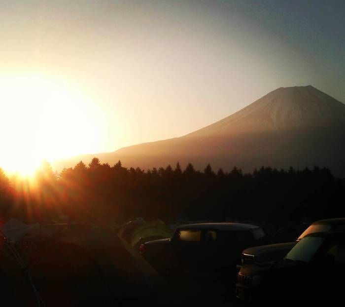 日の出の日差しを浴びる富士山と車