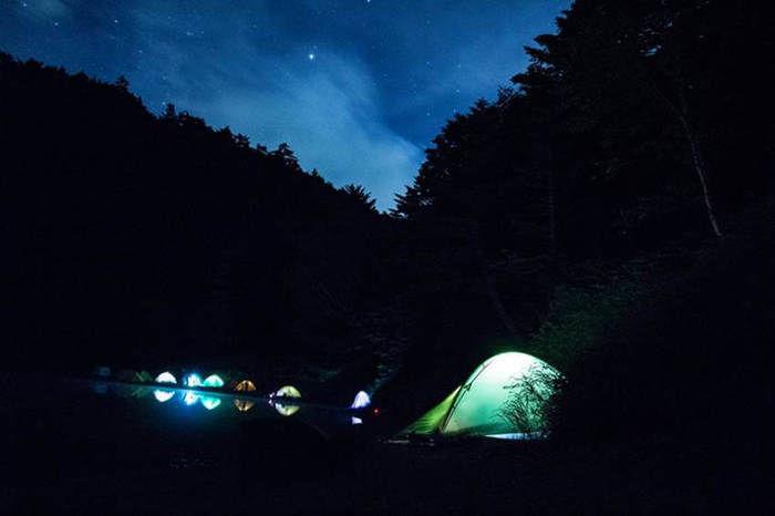 長野県北八ヶ岳の双子池キャンプ場での星空の下、テントが光る様子