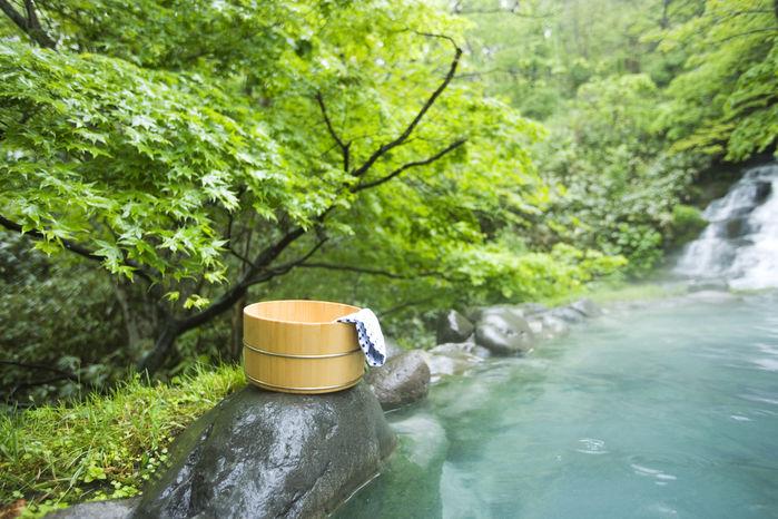 温泉の岩の上に置かれたおけとタオル