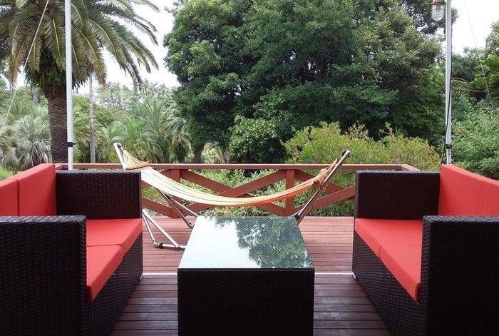 アジアンテイストのソファーとハンモックのあるウッドデッキ