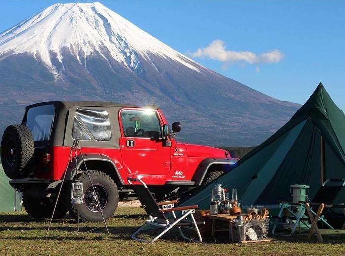 赤いジープと緑のテント