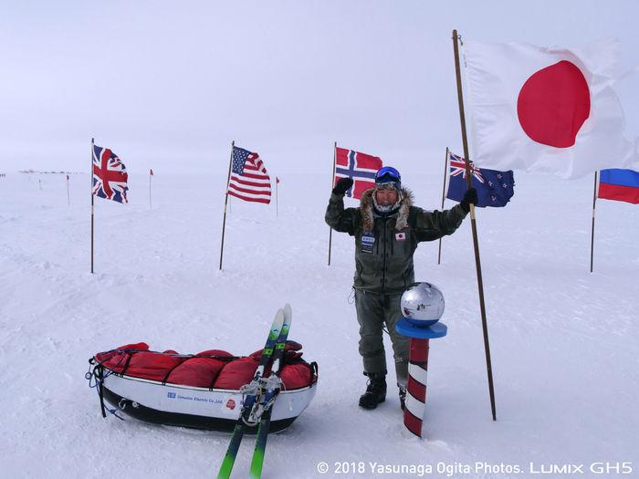 南極で日本の国旗を掲げる荻田泰永さん