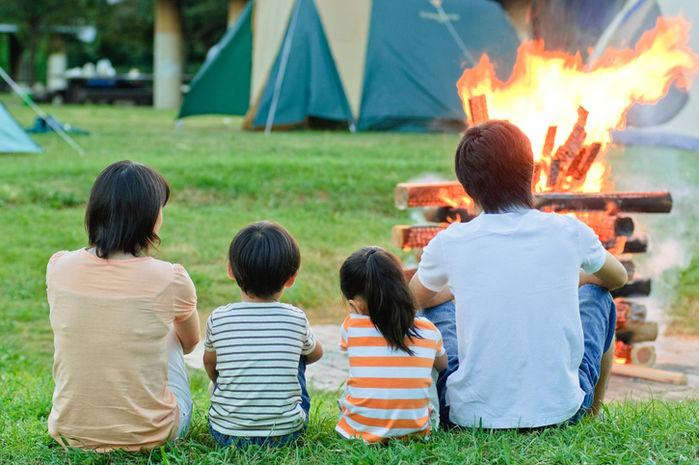 家族でキャンプファイヤーを見ている