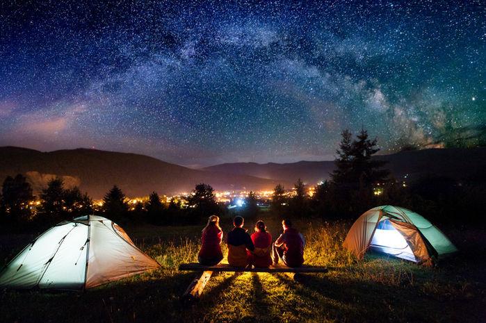 星空の下で座りキャンプを楽しむ人々