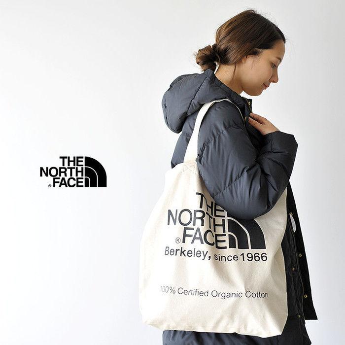 ノースフェイスのトートバッグを肩から下げる女性