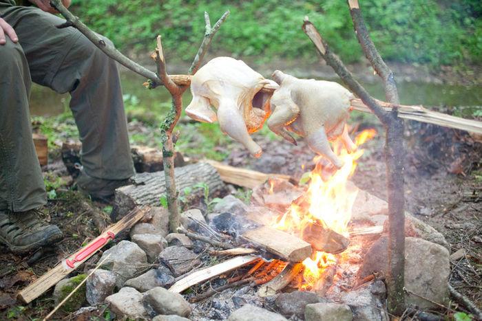 たき火で鶏肉の丸焼きを作る様子