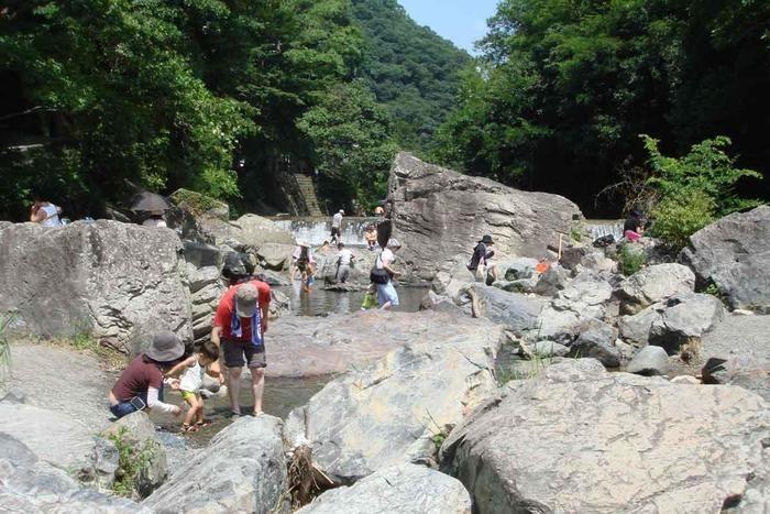 岩場で川遊びをする人々