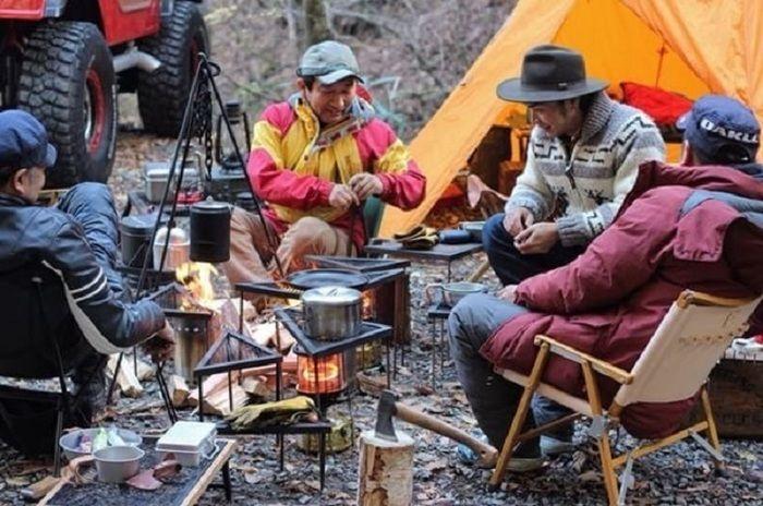ストーブを囲んでくつろぐ男性キャンパー達