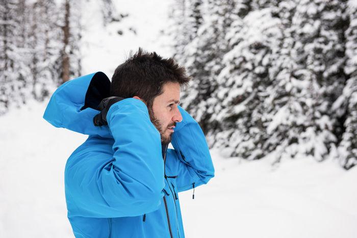 雪上でウェアのフードを被ろうとしている男性