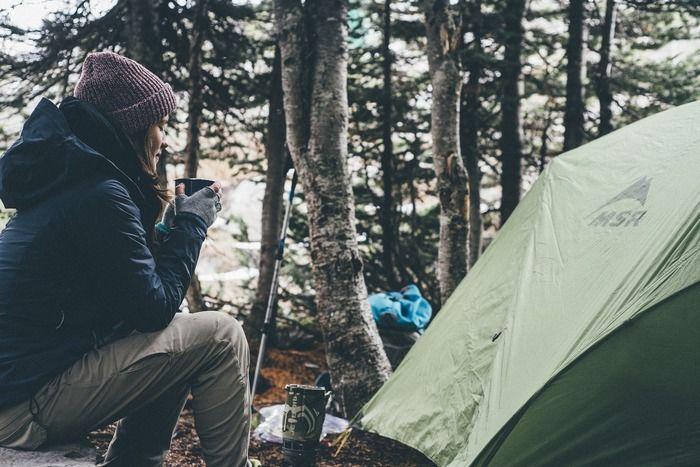 冬キャンプで暖かい飲み物を飲む女性の写真