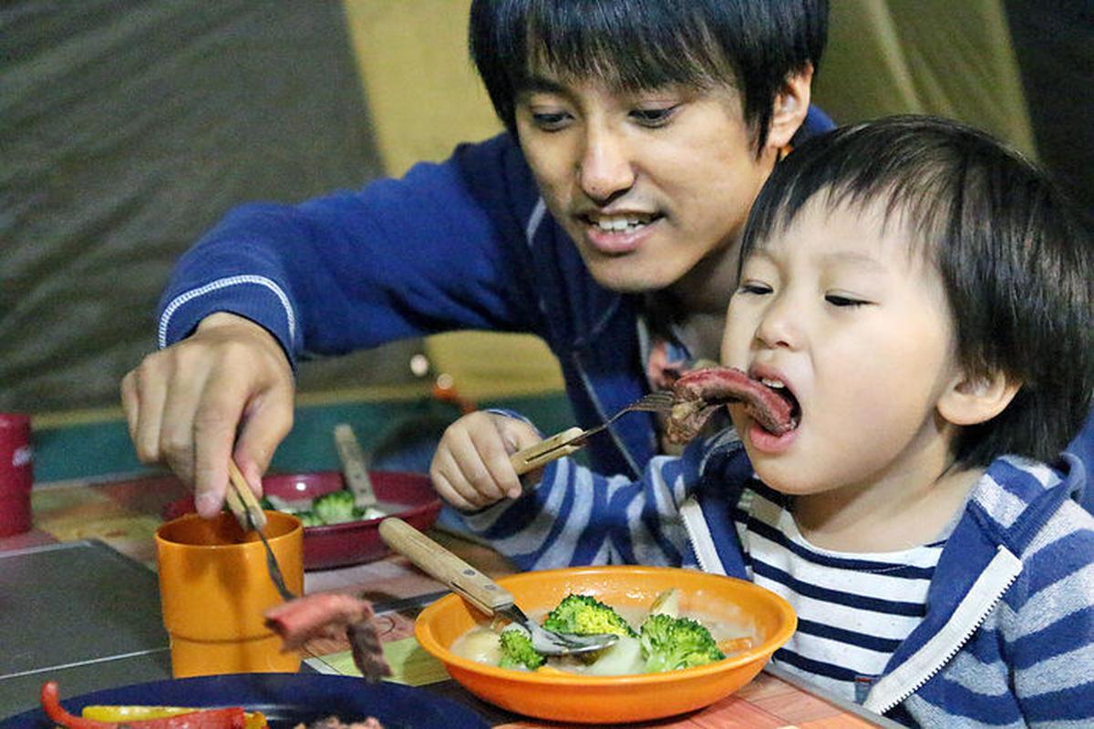 キャンプで食事を楽しむ親子