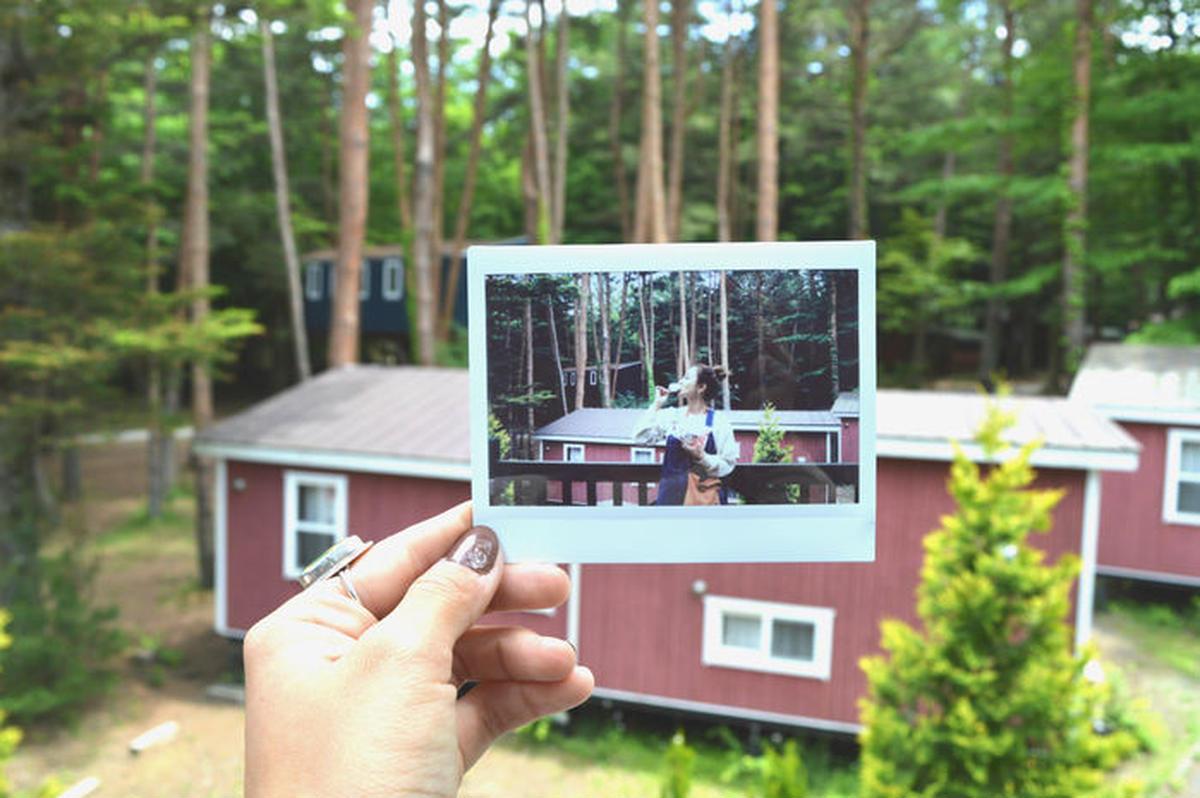 コテージをバックに撮った写真を、そのコテージに重ねて片手に持ち撮ったフォトインフォト