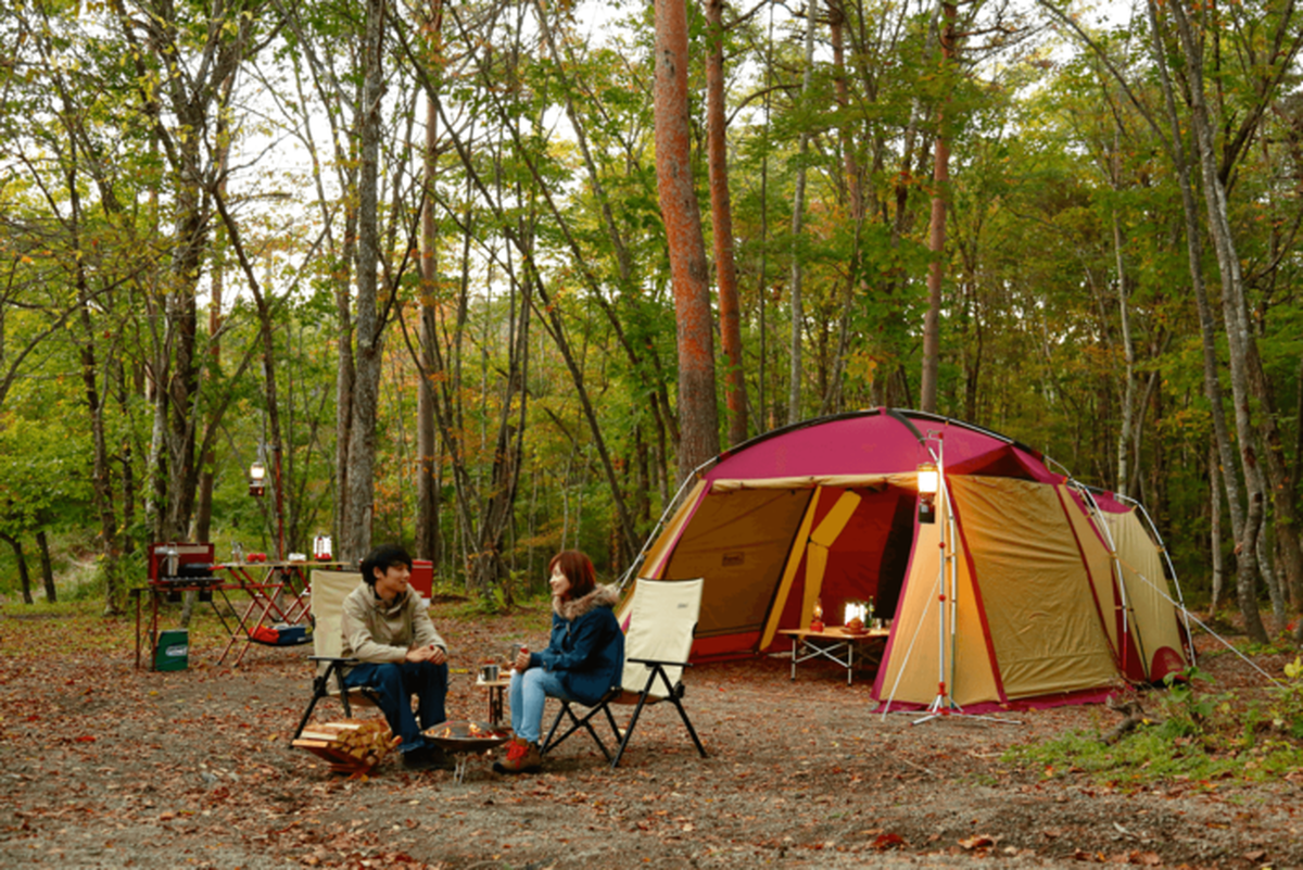 紅葉し始めの森とコールマンのテント